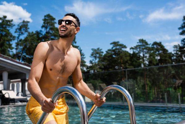 Χαμογελαστός νεαρός με κίτρινο ανδρικό μαγιό σορτς και γυαλιά ηλίου βγαίνει από πισίνα σπιτιού.